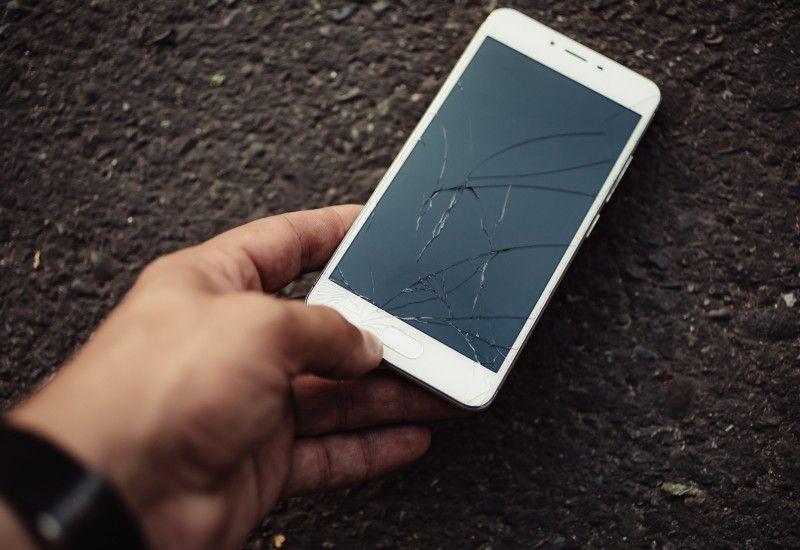 Hånd holder ødelagt telefon