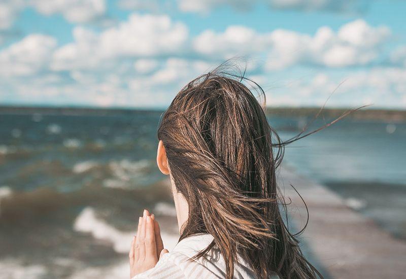 Jente ser ut over havet (Foto: Joshua Reddekopp på Unsplash.com)