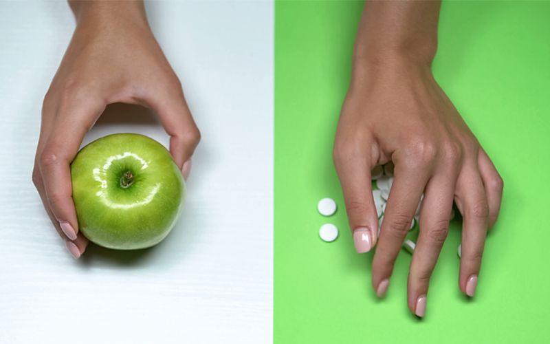 Hånd som velger mellom epler og piller.