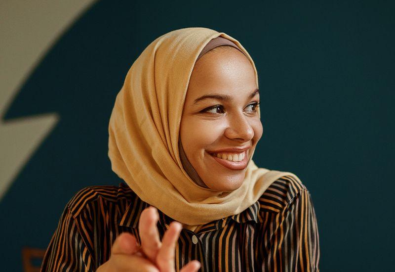 Jente med hijab som smiler.
