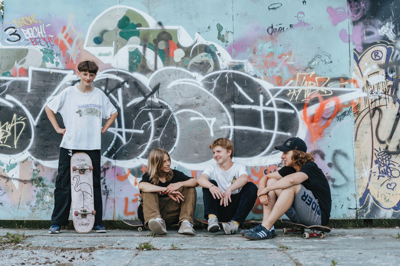 Guttegjeng i ungdomsskolealder henslengt med skateboards foran en nedtagget betongvegg.