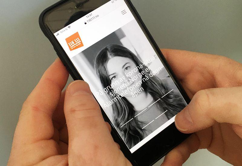 Holder mobil med Alarmtelefonen 116111 åpent (foto: ung.no)