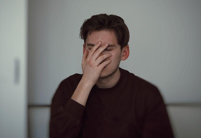 Gutt er misfornøyd og tar seg til ansiktet (foto: Adrian Swancar på unsplash.com)