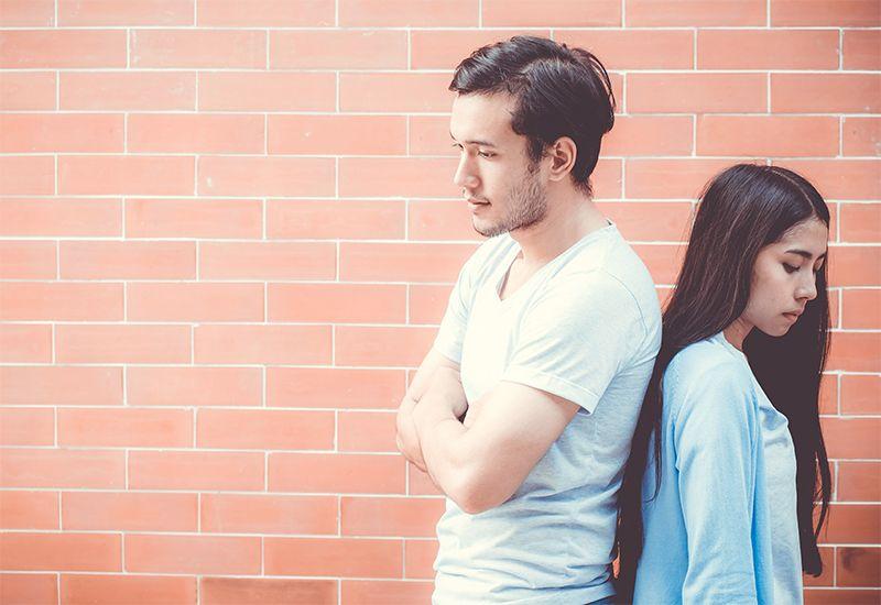 En gutt og jente står med ryggen til hverandre, foran en vegg av brun murstein (Foto: Colourbox.com)