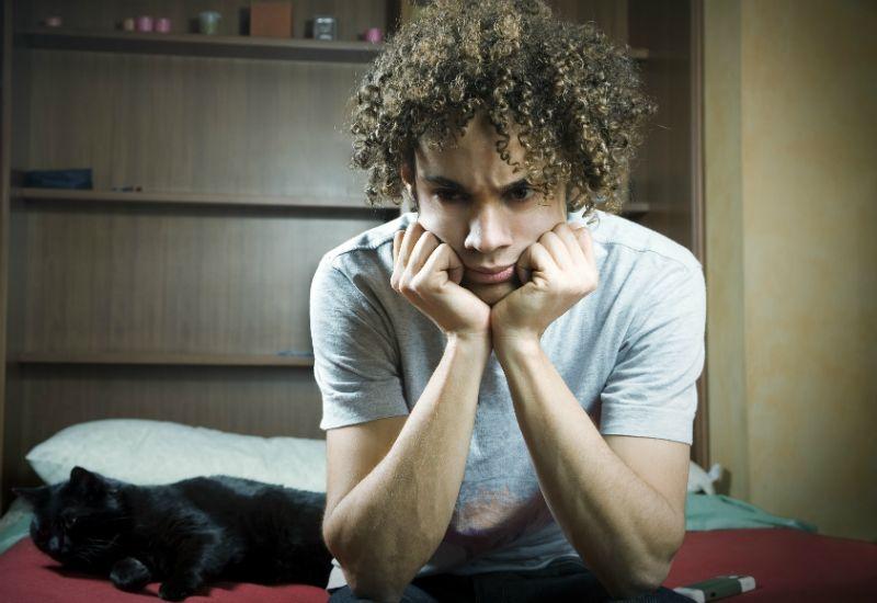 Gutt sitter på sofakanten og tenker. Virker usikker og irritert.