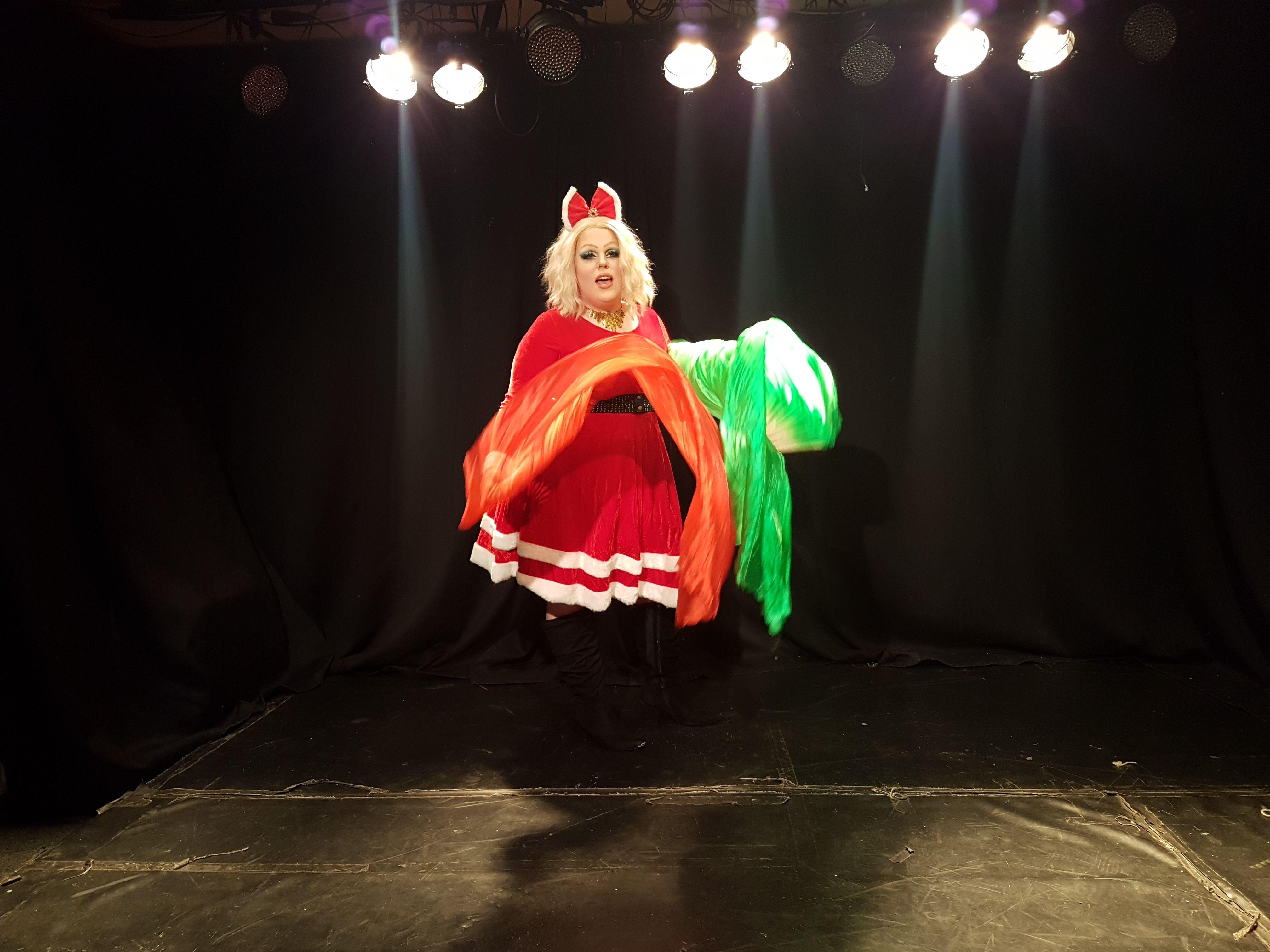 Dragartisten Jaran som Monetta, i rød kjole og med blond parykk (Foto: Ung.no)
