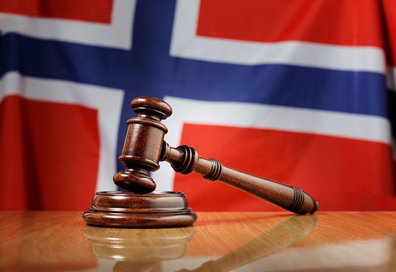 En klubbe ligger på et bord, med det norske flagget i bakgrunnen