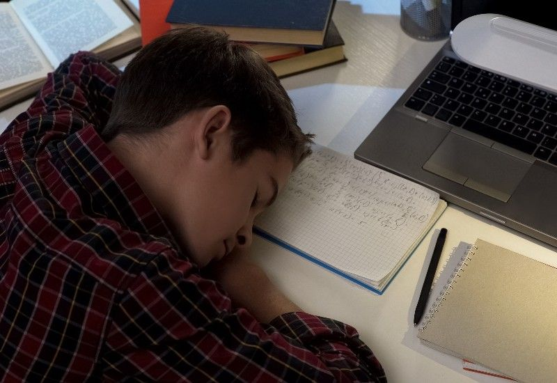 Gutt sover på skolebøkene sine.