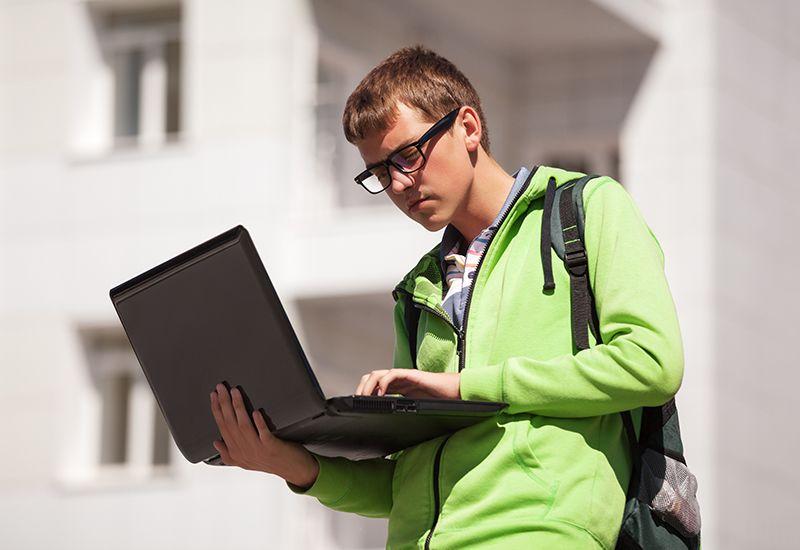 Gutt søker på laptopen sin (colourbox.com)
