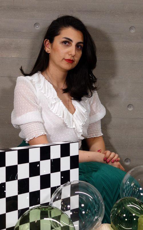 Portrait of Dorna smiling with bright red lipstick.