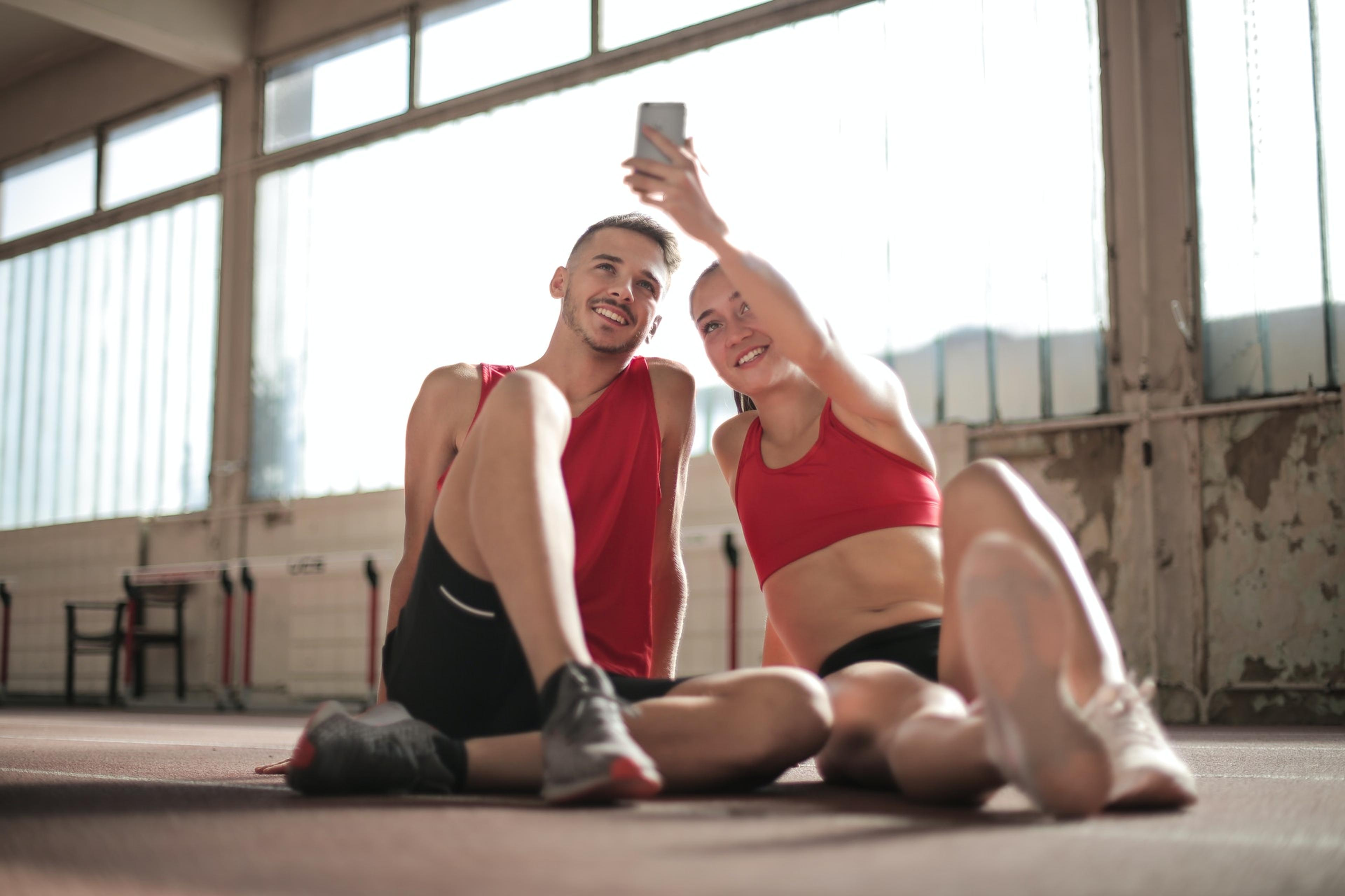 Couple posing at the gym taking selfies