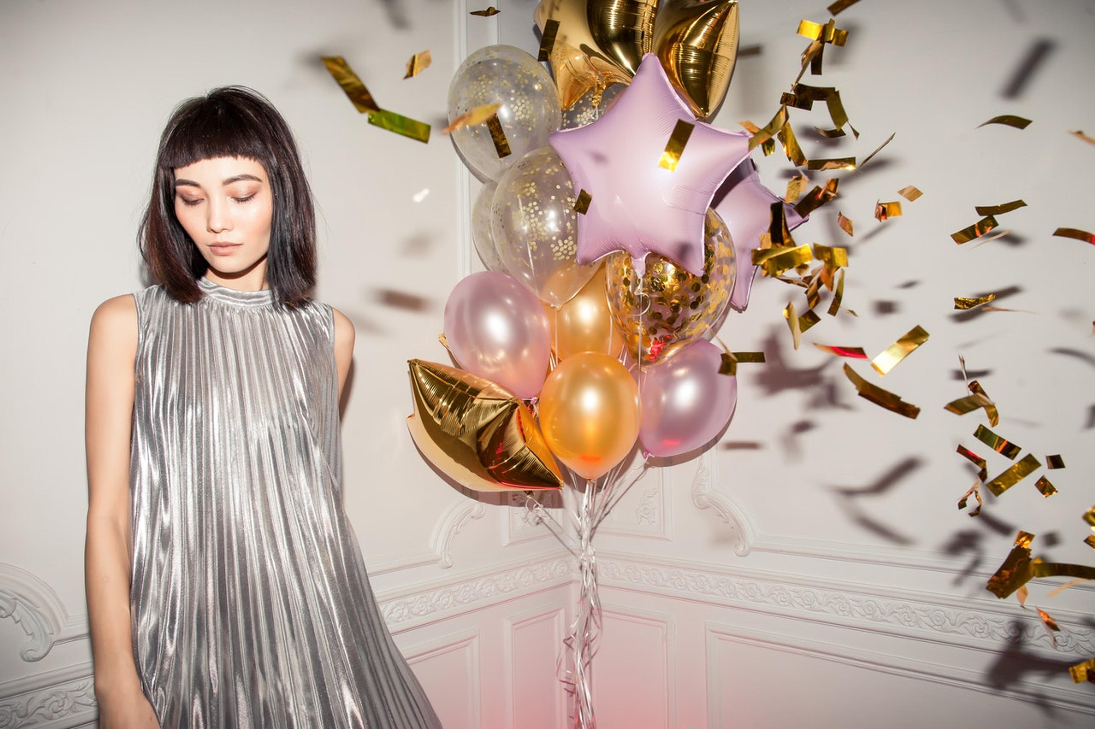 Model posing in front of birthday balloons