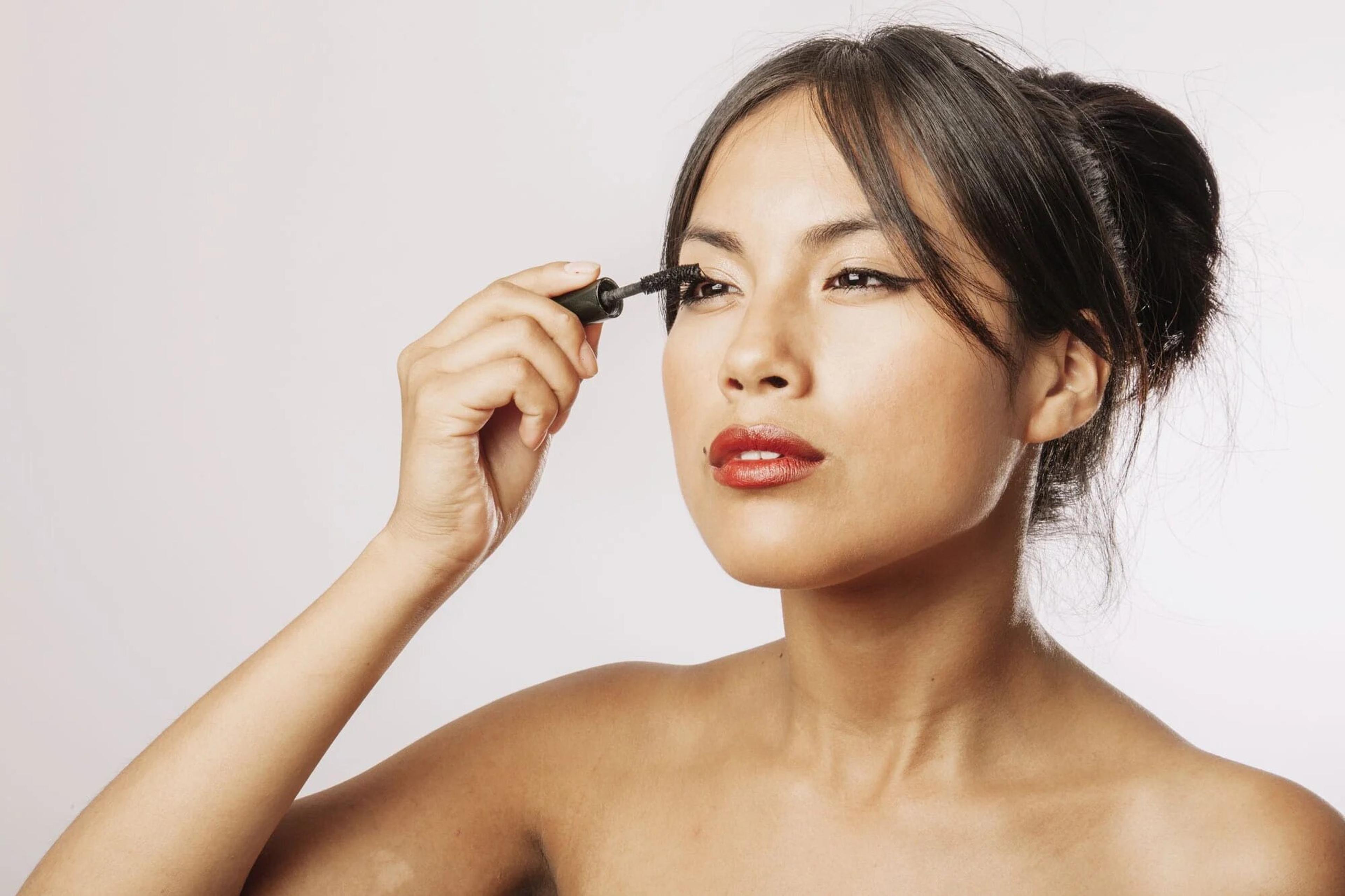 Model applying mascara to her eyes