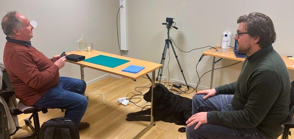 Testrom med to personer som snakker. Testdeltager som holder mobiltelefon.