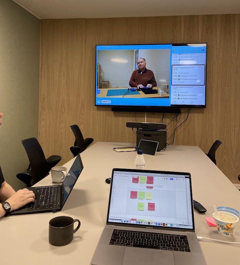To personer sitter i et møterom og observerer brukertest på ekstern skjerm