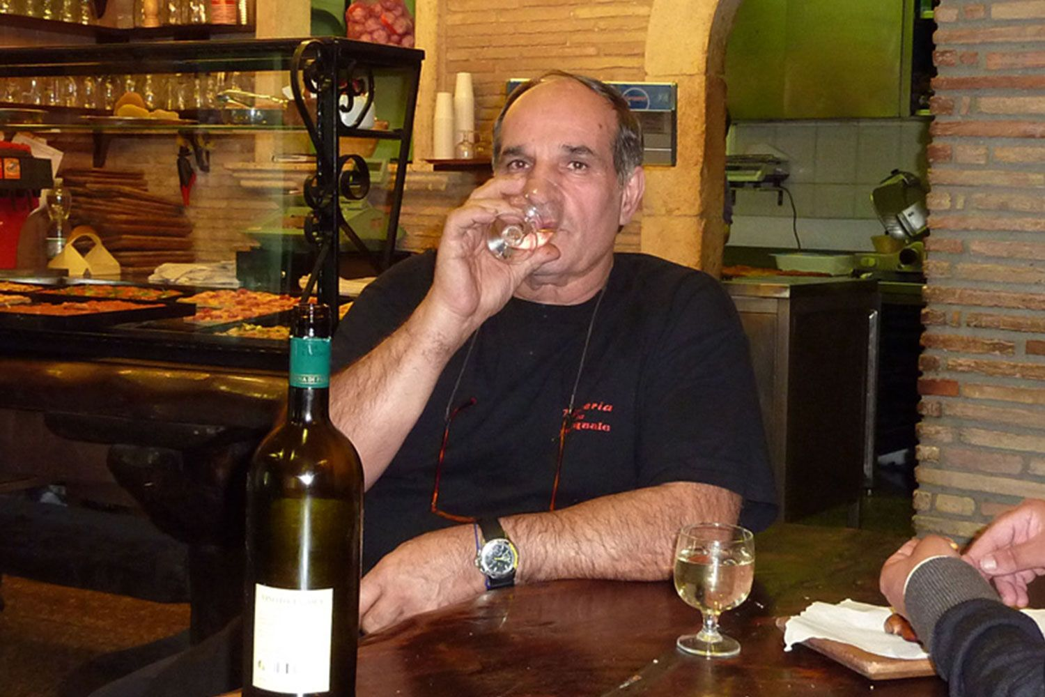 Pasquale enjoying a wine in his pizzeria in Rome.