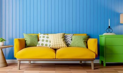 apartment with bright blue wall, yellow couch and green dresser