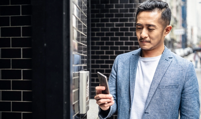 man outside building holding phone next to access reader