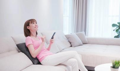 Woman sitting on couch uses smartphone to control smart home devices