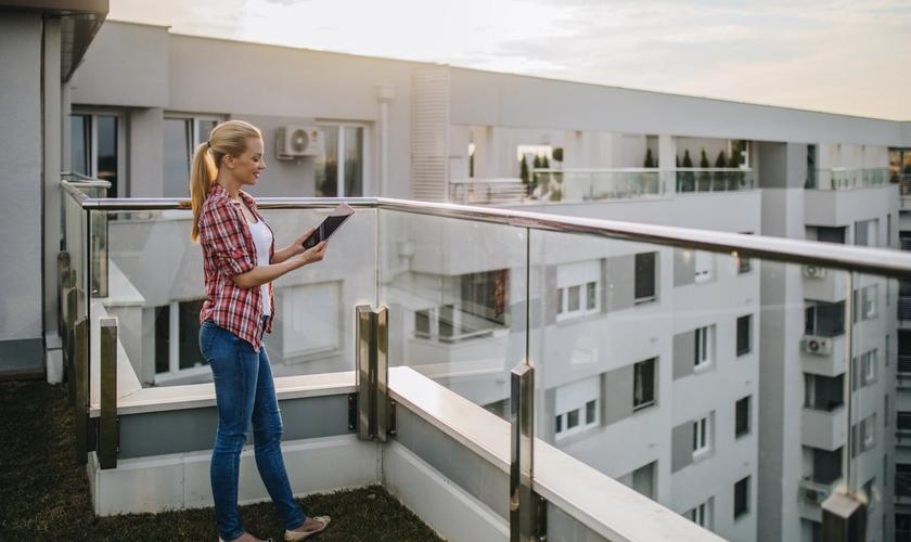 woman looking at tablet on apartment balcony