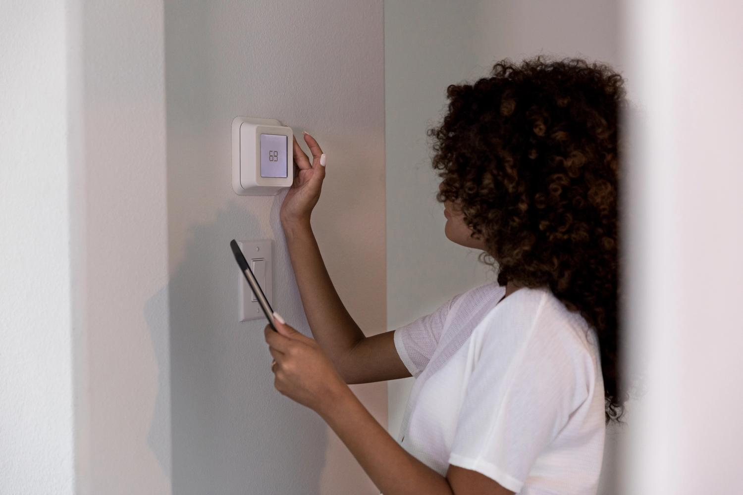 woman using smart thermostat on wall while holding mobile phone