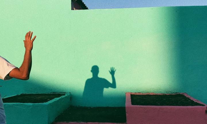 person waving in shadow