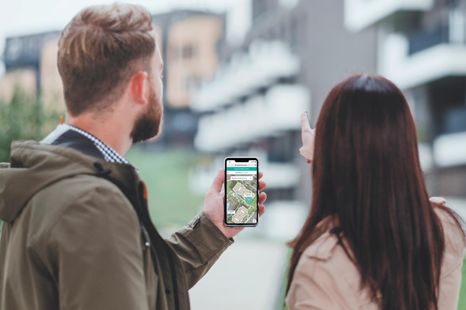 man and woman looking at phone with map pointing forward