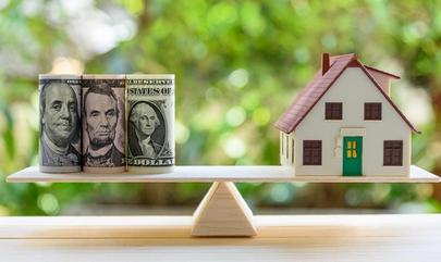 money and house balancing on teeter totter