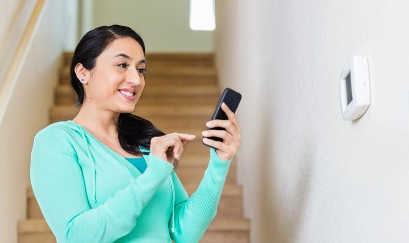 woman standing by thermostat using her phone to control it
