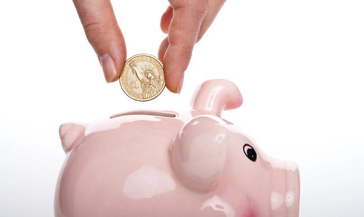 person putting a quarter into pink piggy bank