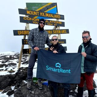 SmartRent trekkers holding up SmartRent flag at peak of Kilimanjaro