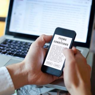 Person holding phone reading terms and conditions of a vendor agreement