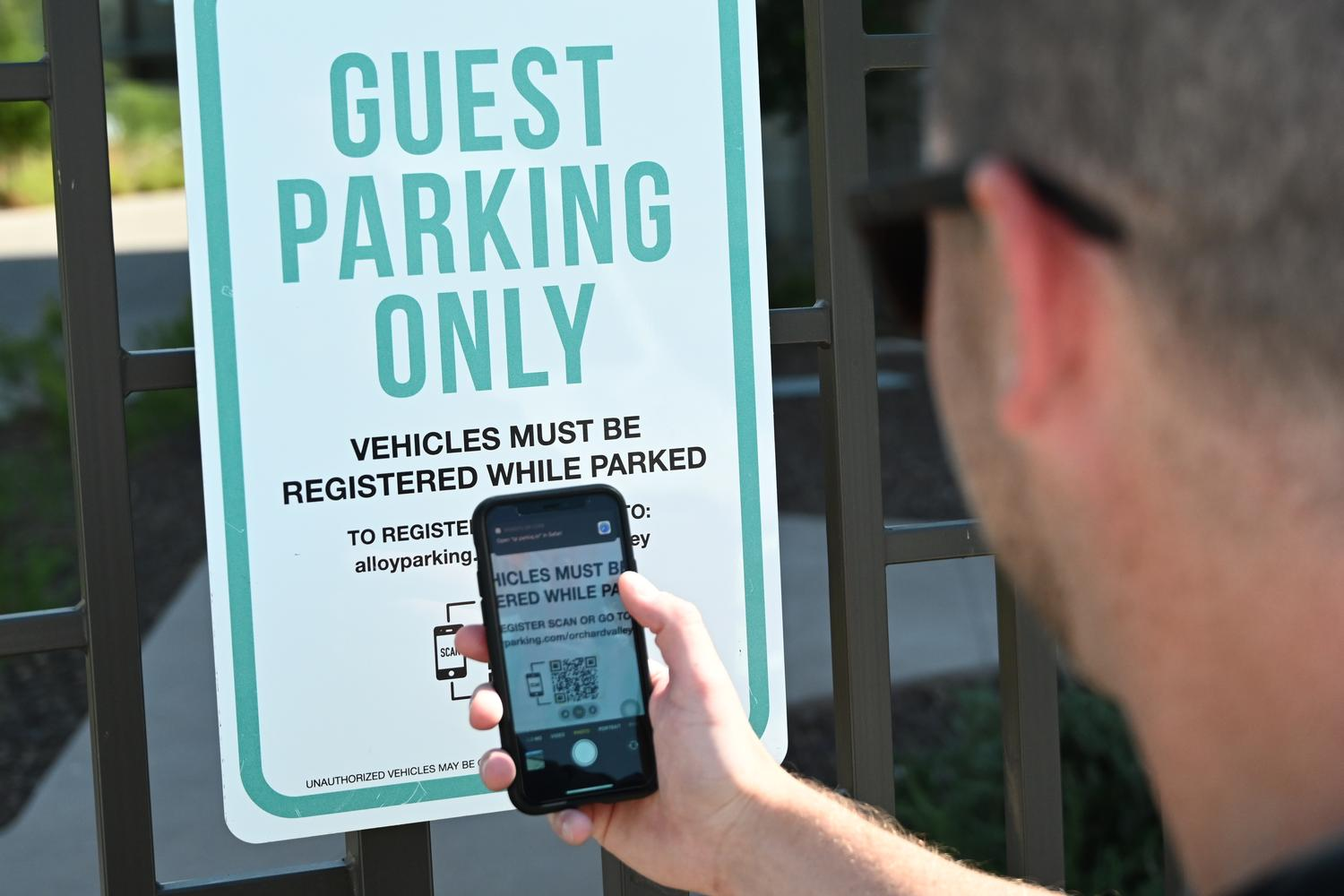 person scanning a guest parking sign with a QR code on smartphone