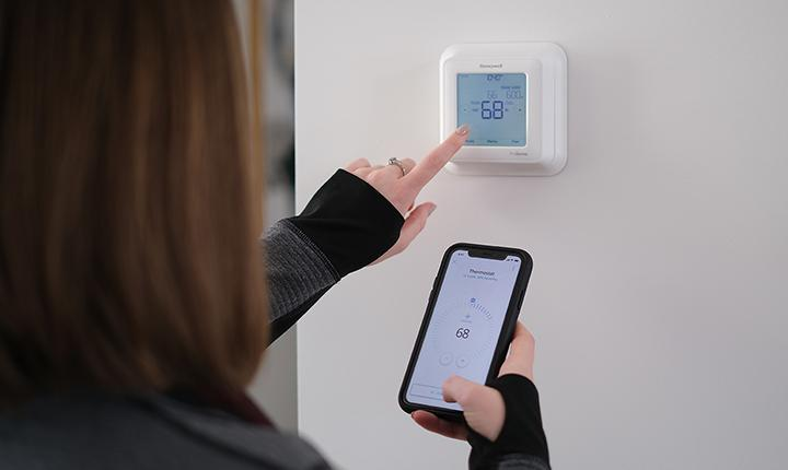 Student operating a smart thermostat
