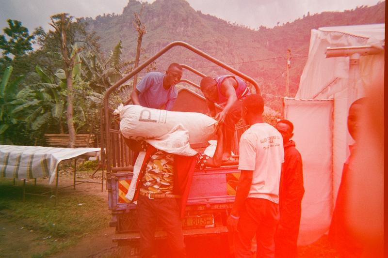 Coffee farmers offloading coffee from a truck. Mount Elgon, Uganda. World Positive Coffee.