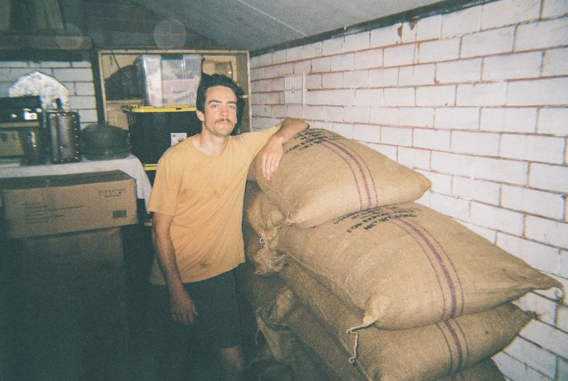 Hamish standing with bags of Zukuka Bora coffee from Mount Elgon.