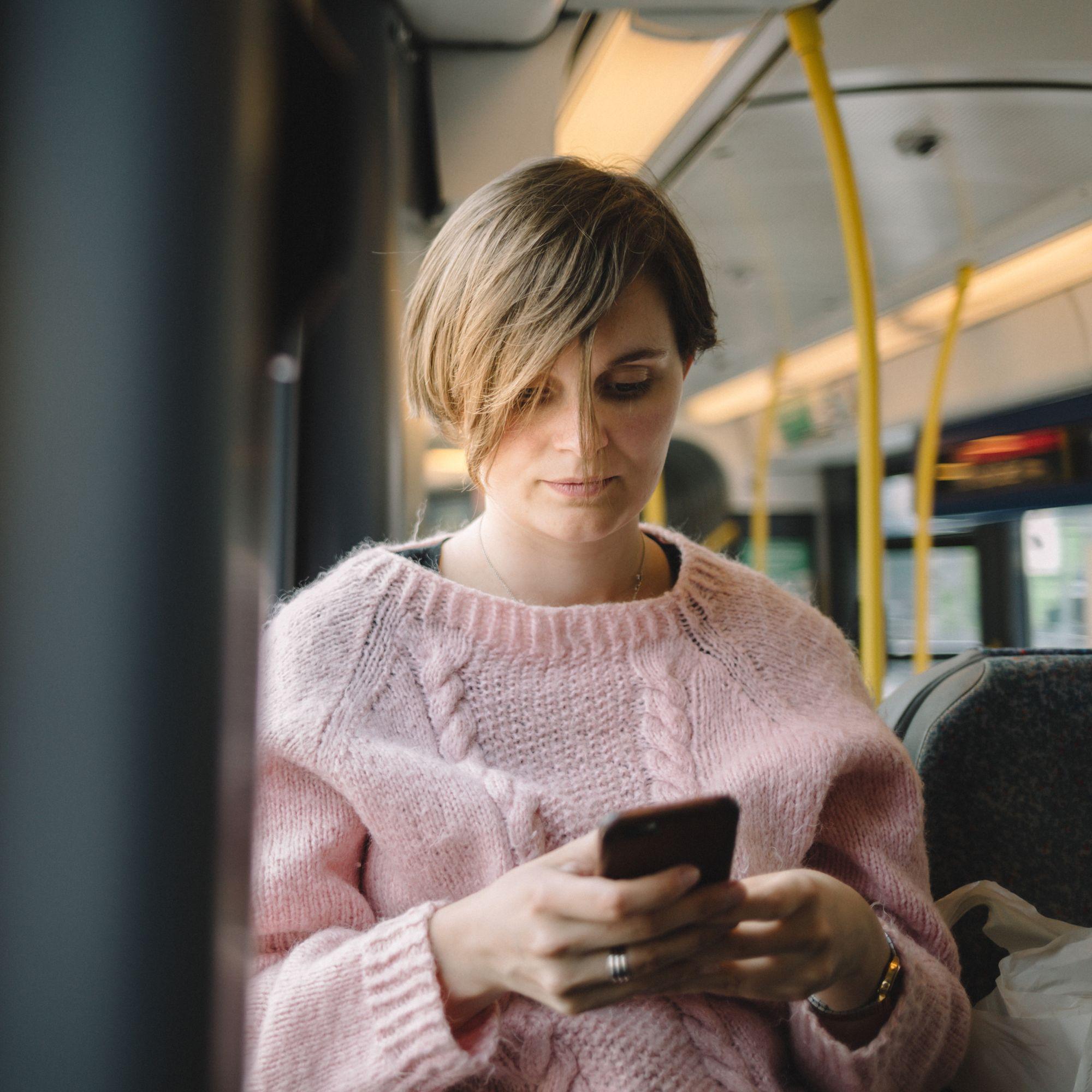 Eksempelbilde: En kvinne som bruker mobil på bussen.