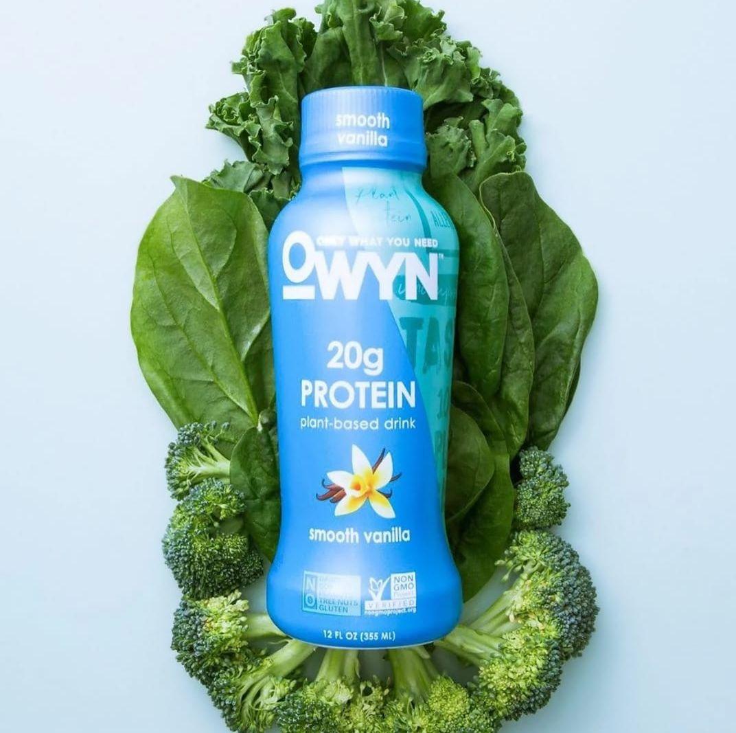 OWYN Smooth Vanilla Protein Shake laying on leafy greens