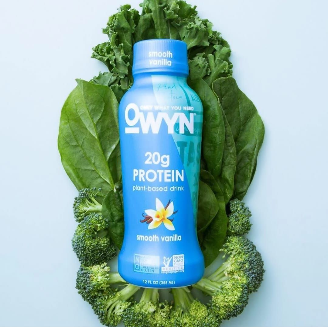 OWYN Smooth Vanilla Protein Shake laying on leafy greens
