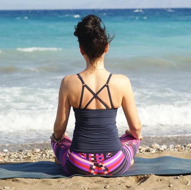 Meditating woman at the beach