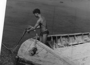 Male figure in boat pulling on rope [P25]