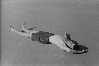Male figure in bathing shorts lying on beach [P58]