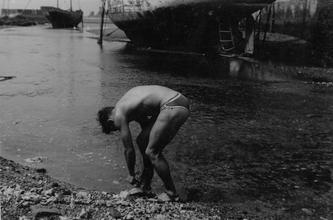 Male figure crouching at water's edge [P52]