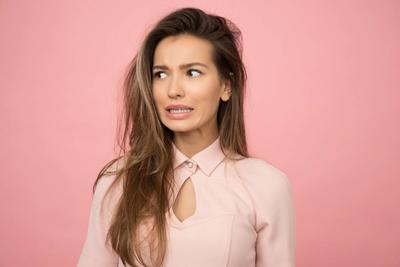woman wearing peach shirt blending to its peach colored background