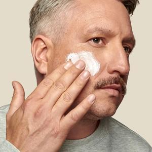 Bilde av mann som smører krem i ansiktet.