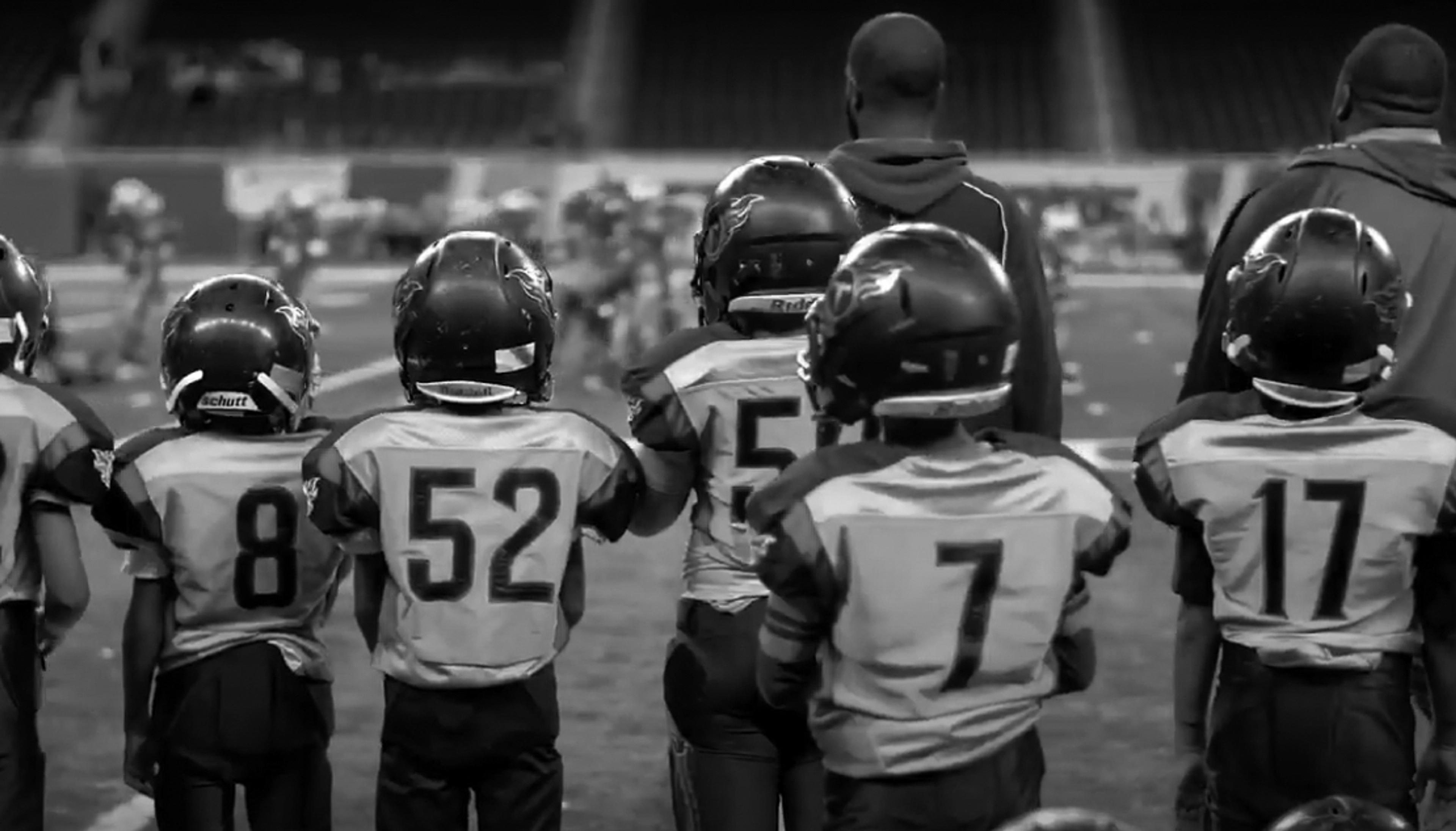 Young Football players on the sideline of a game shot the Detroit PAL Get in the Game Video