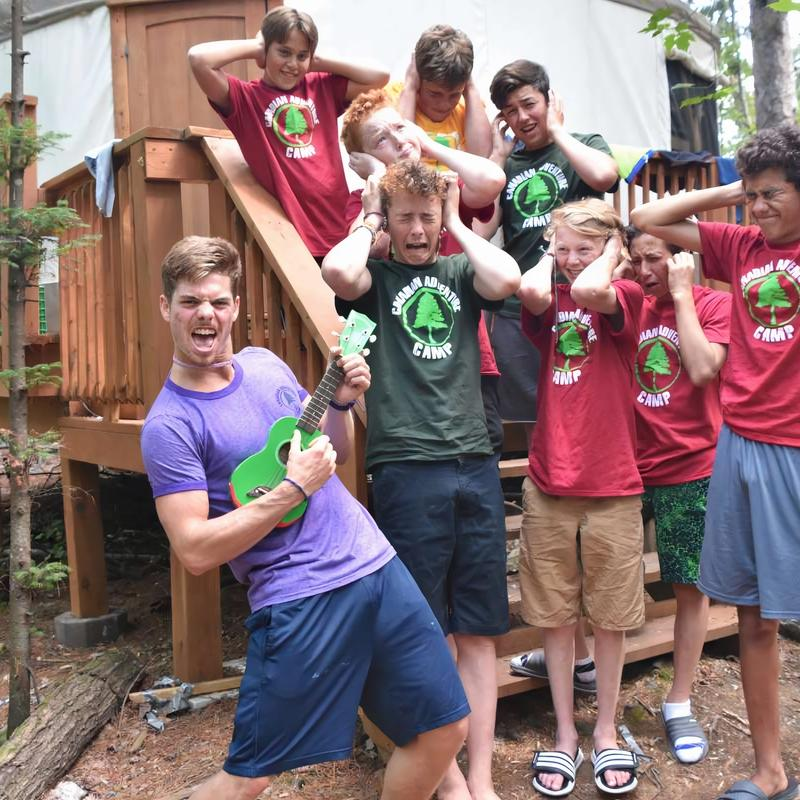 cabin group photo with counsellor playing guitar and campers covering their ears