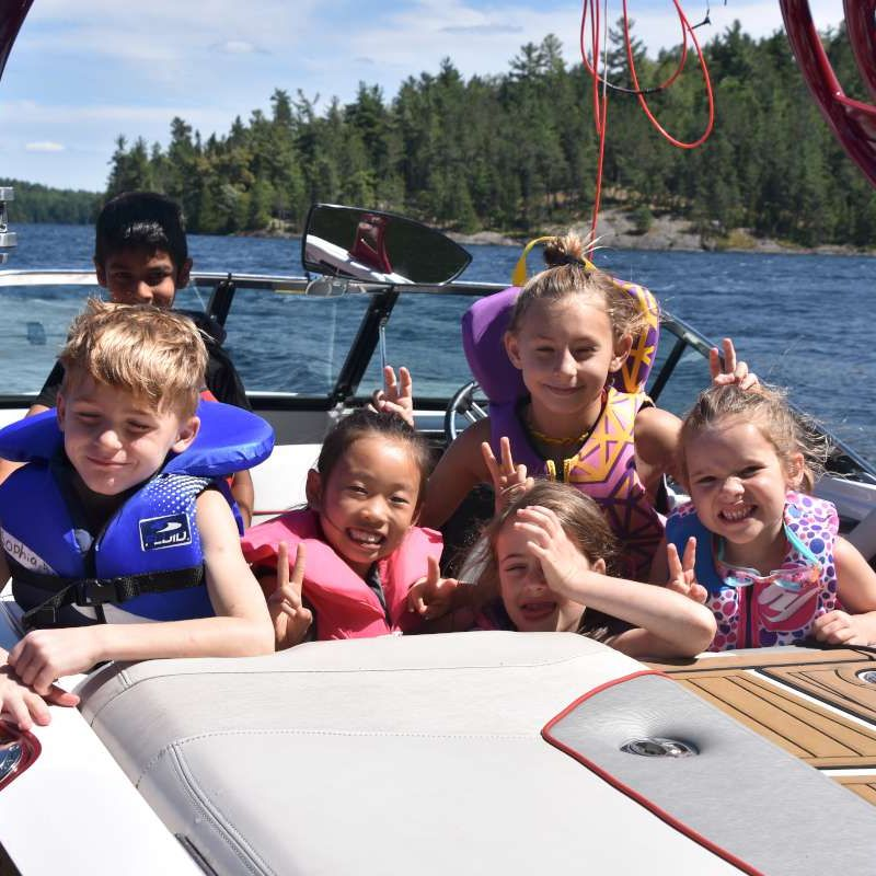 group of young campers on a boat smiling at the camera at Canadian Adventure Camp