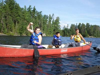 staff and camper canoeing and smiling at Canadian Adventure Camp