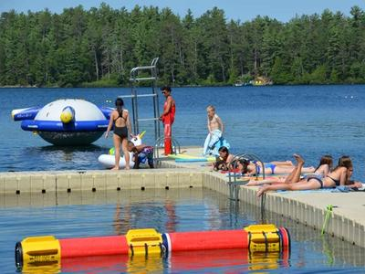 campers lying in the sun while lifeguard watches at Canadian Adventure Camp